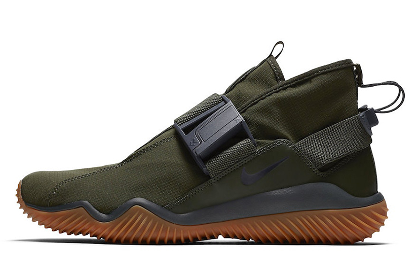 a9c0a419a7ae This Nike KMTR features an Olive-based upper that comes with its signature  buckle strap